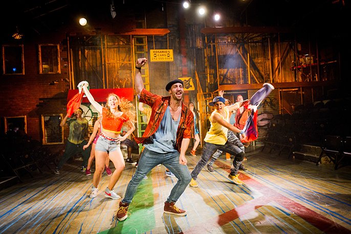 Sam Mackay as Usnavi and The Company of IN THE HEIGHTS. Photo Credit Robert Workman
