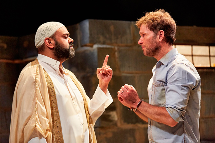 The Invisible Hand at The Tricycle Theatre. Tony Jayawardena (Imam Saleem), Daniel Lapaine (Nick). Photo by Mark Douet
