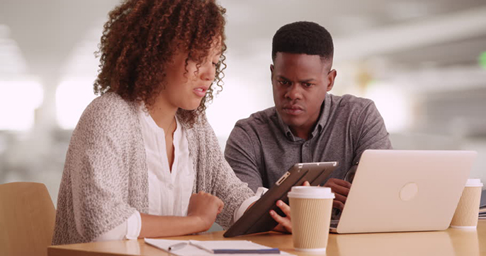 Black man and woman in their 20s working at contemporary office using technology